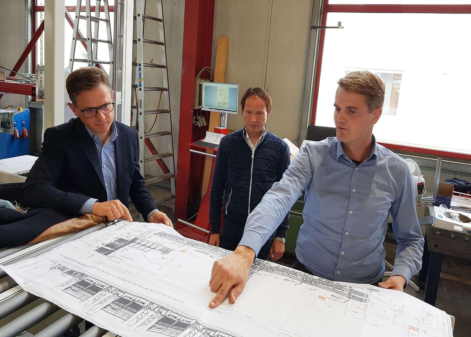 Benedikt Rotte veranschaulicht Carsten Linnemann eine Automatisation für einen großen Küchenhersteller aus OWL